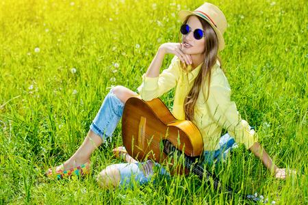 mujeres fashion: Sonriente niña romántica, sentado en una hierba y tocar la guitarra. Día de verano.