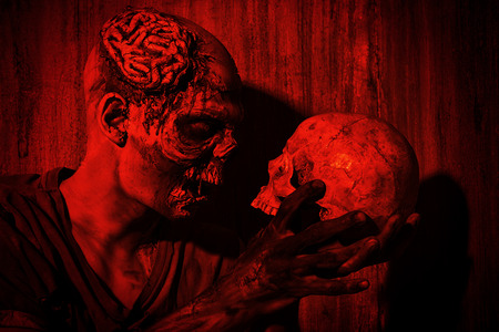frightening: Frightening bloody zombie man with a skull in blood-red light. Halloween. Stock Photo