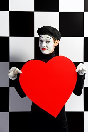 mimo: Retrato de un mimo masculina sostiene el amor que expresa corazón rojo grande. Fondo tablero de ajedrez. Foto de archivo