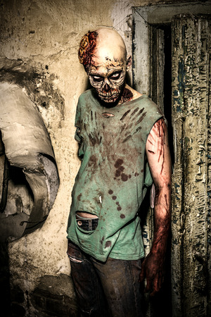 spooky eyes: Horrible scary zombie man on the ruins of an old house. Horror. Halloween.
