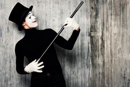 pantomima: Elegante mimo masculina expresiva posando con el bastón por una pared del grunge. Foto de archivo