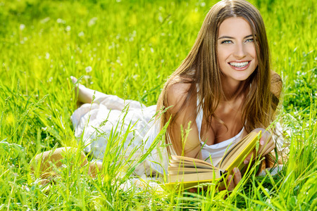 a serene life: Beautiful happy young woman lying on a grass in the summer park and smiling. Holidays, vacation.