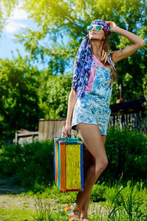 valise voyage: Jeune fille romantique avec lumineux valise rayé debout en plein air entouré d'arbres verdoyants. Couleurs d'été. tir de mode.