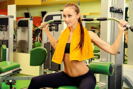 bodycare: Beautiful slender young woman is training at the gym. Active lifestyle, bodycare. Fitness equipment. Stock Photo