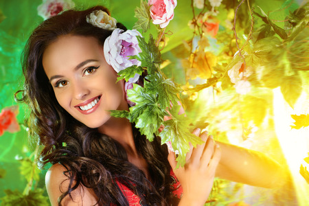 summer beauty: Happy beautiful brunette woman among summer plants and flowers. Beauty, fashion. Spa, healthcare. Tropical vacation. Stock Photo