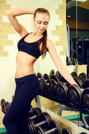 bodycare: Beautiful young woman with perfect figure is training with dumbbells at the gym. Active lifestyle, bodycare. Fitness equipment.