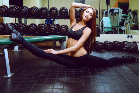 active lifestyle: Slender girl doing stretching exercises at the gym. Active lifestyle, bodycare. Perfect figure.