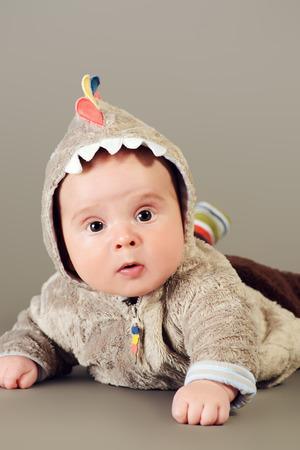 baby dragon: Beautiful little baby lying on a floor. Kids fashion. Happy childhood. Studio shot.