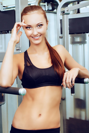 active lifestyle: Beautiful slender young woman is training at the gym. Active lifestyle, bodycare. Fitness equipment. Stock Photo