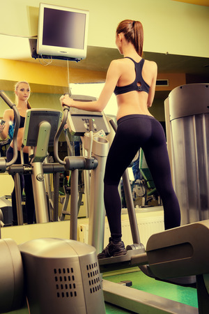 active lifestyle: Attractive young woman is training on a treadmill in a fitness club. Active lifestyle, bodycare. Fitness equipment.