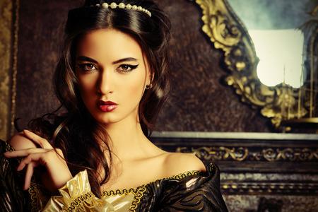 vestido medieval: Estilo Renacimiento - hermosa mujer joven en el vestido caro exuberante en un antiguo palacio interior. Estilo vintage. Moda.