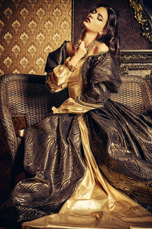 history: Renaissance Style -  beautiful young woman in the lush expensive dress in an old palace interior. Vintage style. Fashion.