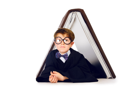 graduation suit: Cute student boy in graduation suit lying under the huge book. Educational concept. Isolated over white. Stock Photo