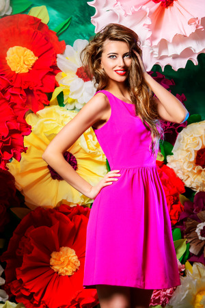 summer beauty: Portrait of a beautiful happy young woman posing on a background of bright large flowers. Beauty, fashion. Summer inspiration.