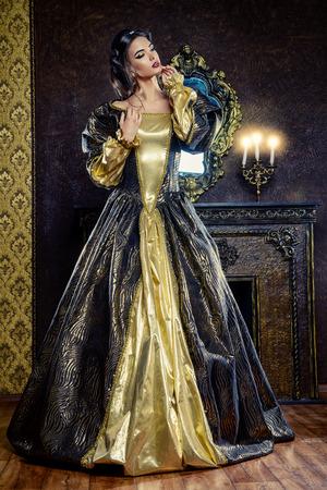 princesa: Estilo Renacimiento - hermosa mujer joven en el vestido caro exuberante en un antiguo palacio interior. Estilo vintage. Moda.
