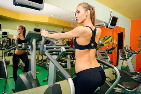 Attractive young woman is training on a treadmill in a fitness club. Active lifestyle, bodycare. Fitness equipment.