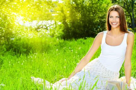 vida natural: Mujer joven sentada sobre la hierba en el parque de verano Hermosa sonrisa. Ella es absolutamente feliz. Foto de archivo