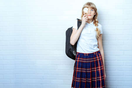 blonde teenager: Cute teen girl in school uniform looking through a magnifying glass. Education. Studio shot. Stock Photo