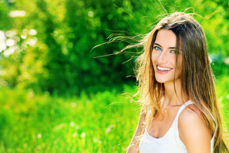woman healthy: Beautiful smiling young woman sitting on a grass in the summer park. She is absolutely happy.
