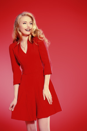 red hair beauty: Charming smiling young woman in red dress and with blonde curled hair. Beauty, fashion. Cosmetics, make-up. Red background. Stock Photo