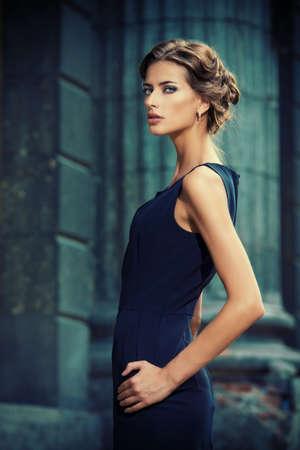 moda: modelo Vogue vestindo vestido preto que levanta sobre o fundo urbano. Forme o tiro.