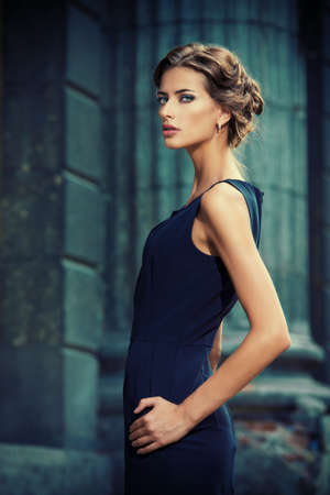 divat: Vogue modell visel fekete ruha jelentő több mint városi háttérben. Divat lövés.