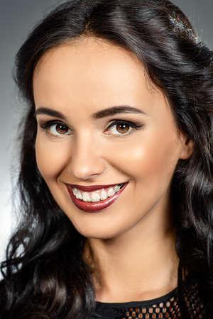 dientes sanos: Retrato de mujer joven con una hermosa sonrisa y dientes sanos. Apoyos dientes. Estudio de disparo.