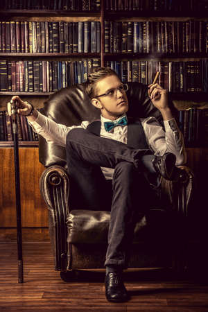 armchairs: Elegant young man in a suit sitting in armchair and smoking a cigar. Vintage room. Fashion.