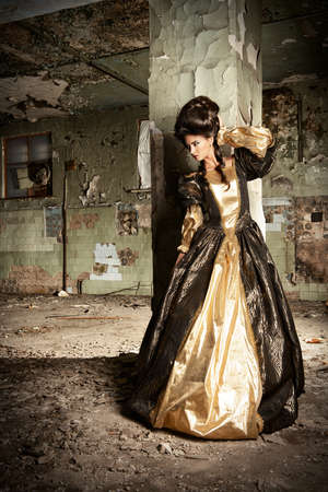 historical: Art Fashion. Beautiful young woman in elegant historical dress and with barocco updo hairstyle posing in the ruins of the castle. Renaissance. Barocco.