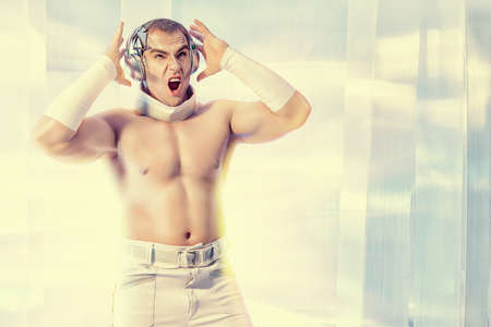 expressive: Expressive futuristic muscular man dancing and singing in headphones on a luminous transparent background. Music, technology. Futuristic DJ.
