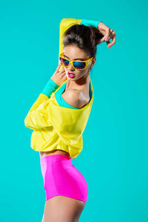 glasses model: Expressive fashion model posing in vivid colourful clothes. Bright fashion. Optics, eyewear. Studio shot.