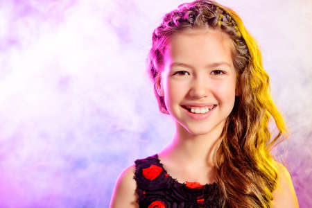 cabello rizado: Retrato de una muchacha adolescente sonriente hermosa con un hermoso pelo largo y rizado. Belleza, la moda infantil. Estudio de disparo.