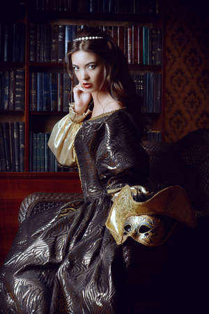 woman hairstyle: Renaissance Style -  beautiful young woman in the lush expensive dress in an old palace interior. Vintage style. Fashion.