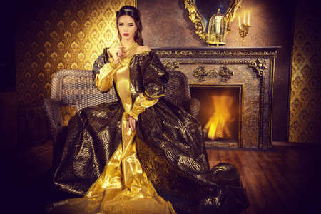 aristocrat: Renaissance Style -  beautiful young woman in the lush expensive dress in an old palace interior. Vintage style. Fashion.