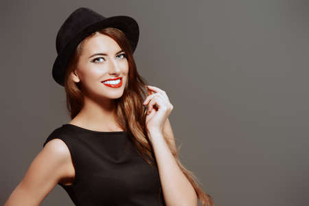 girl: Joyful pretty girl wearing black dress and black classic hat smiling at camera. Beauty, fashion concept. Hipster style. Stock Photo