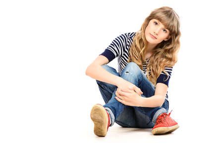 fashion girl style: Full length portrait of a pretty teenager girl sitting on a floor. Isolated over white.