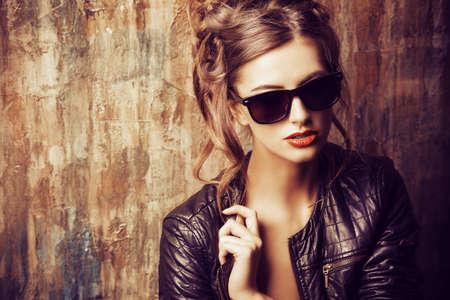 時尚: 時尚拍了一個美麗的年輕女子,穿著黑色皮夾克和墨鏡。 版權商用圖片