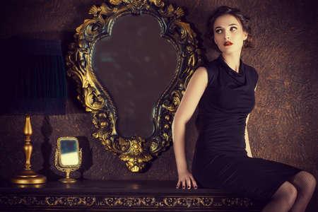 anochecer: Mujer joven elegante en vestido de noche negro posando en interior de la vendimia