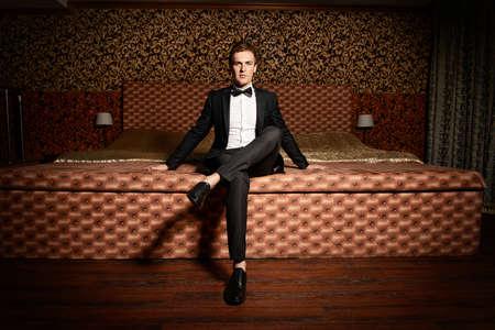 Stilig man i elegant kostym sitter på en säng Stockfoto
