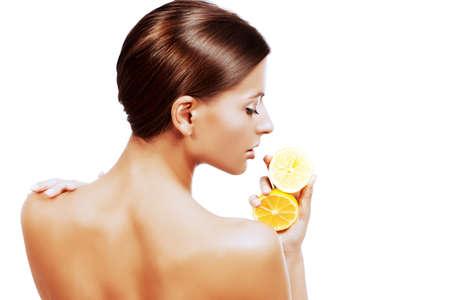 personas de espalda: Mujer delgada hermosa que sostiene jugosos limones frescos. Estilo de vida saludable. Alimentación saludable. Frutas y vegetales. Concepto de cuidado del cuerpo. Aislado en blanco.
