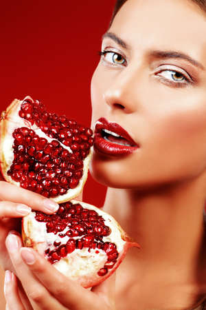 juicy: Attractive young woman eating fresh pomegranate Stock Photo