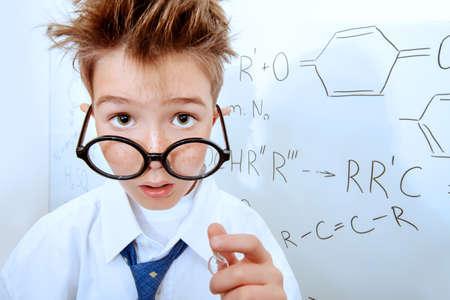 atomo: Colegial divertido en grandes vasos de pie por el consejo escolar. Química. Ciencia y educación.