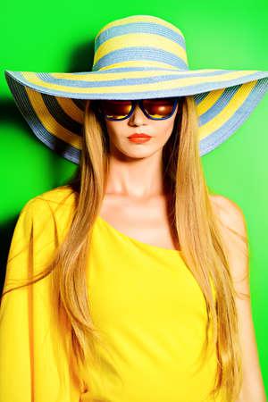 Bella dama de moda con un vestido de color amarillo brillante sobre fondo verde. Belleza, concepto de moda. Óptica. Las vacaciones de verano. Foto de archivo