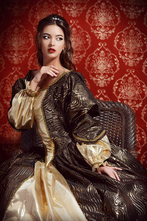 historical clothing: Beautiful young lady in the lush expensive dress posing over vintage background. Renaissance. Barocco. Fashion. Stock Photo