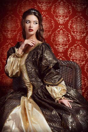 Señora joven hermosa en el vestido caro exuberante que presenta sobre el fondo de la vendimia. Renacimiento. Barocco. Moda.