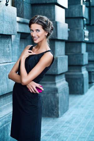 mujer elegante: Modelo de Vogue con un vestido negro posando sobre fondo urbano. Disparo de moda. Foto de archivo