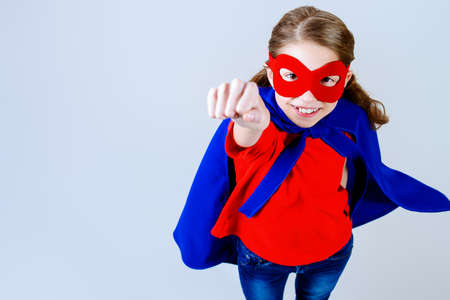 supergirl: Cute girl teenager in a costume of superhero. Isolated over white background.