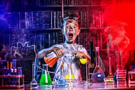 biotecnologia: Un niño haciendo experimentos en el laboratorio. Explosión en el laboratorio. Ciencia y educación.