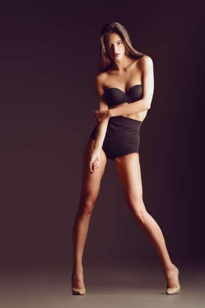 brunette: Hermosa mujer atractiva delgada en lencería sexy negro. Moda foto de estudio.