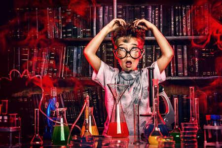 experimento: Un ni�o haciendo experimentos en el laboratorio. Explosi�n en el laboratorio. Ciencia y educaci�n.
